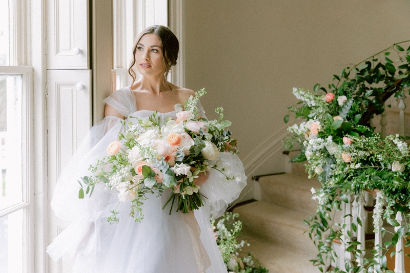 Wedding Officiant in NYC, bride standing next to window holding bouquet