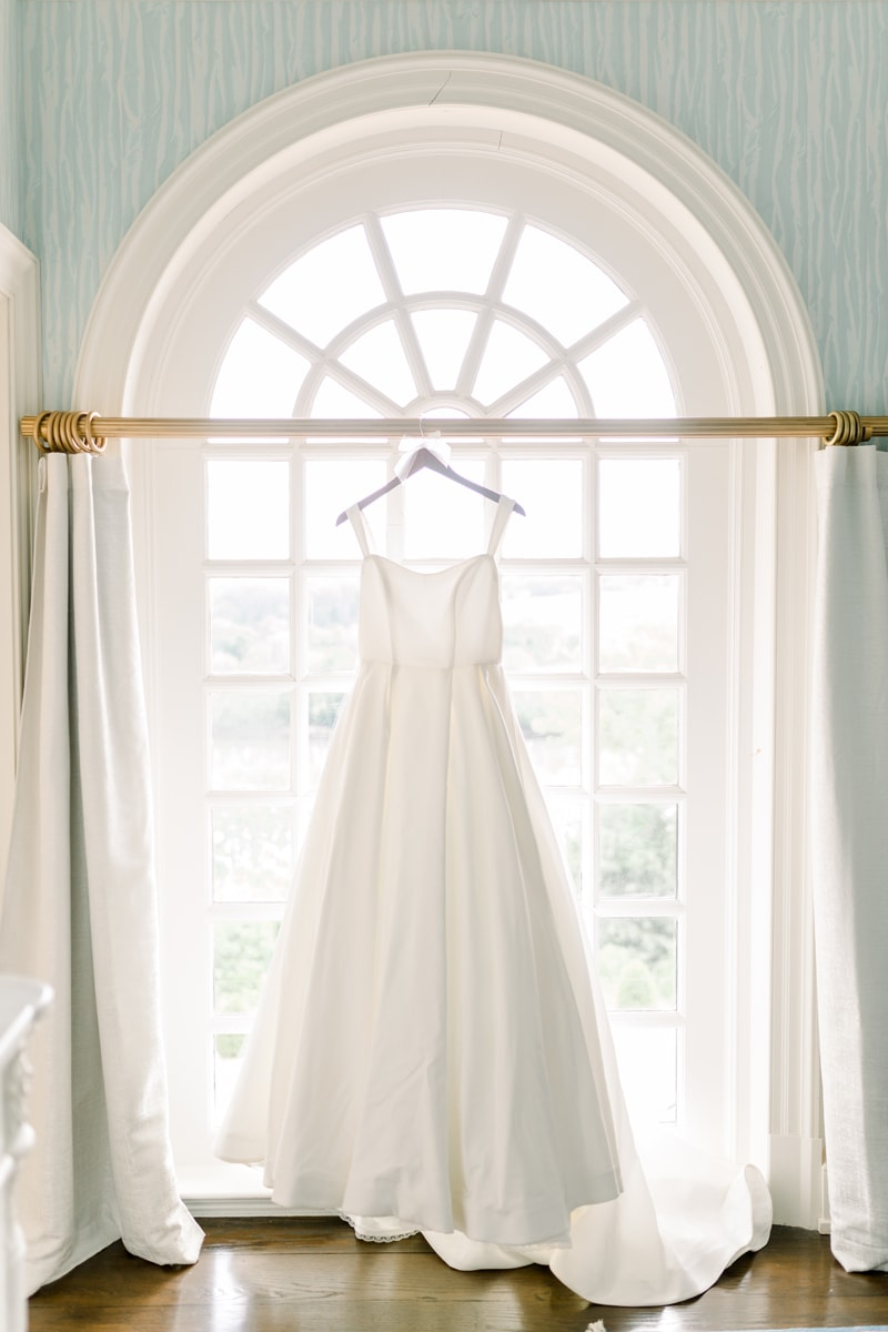 New York Wedding Officiant, bridal gown hanging up in window